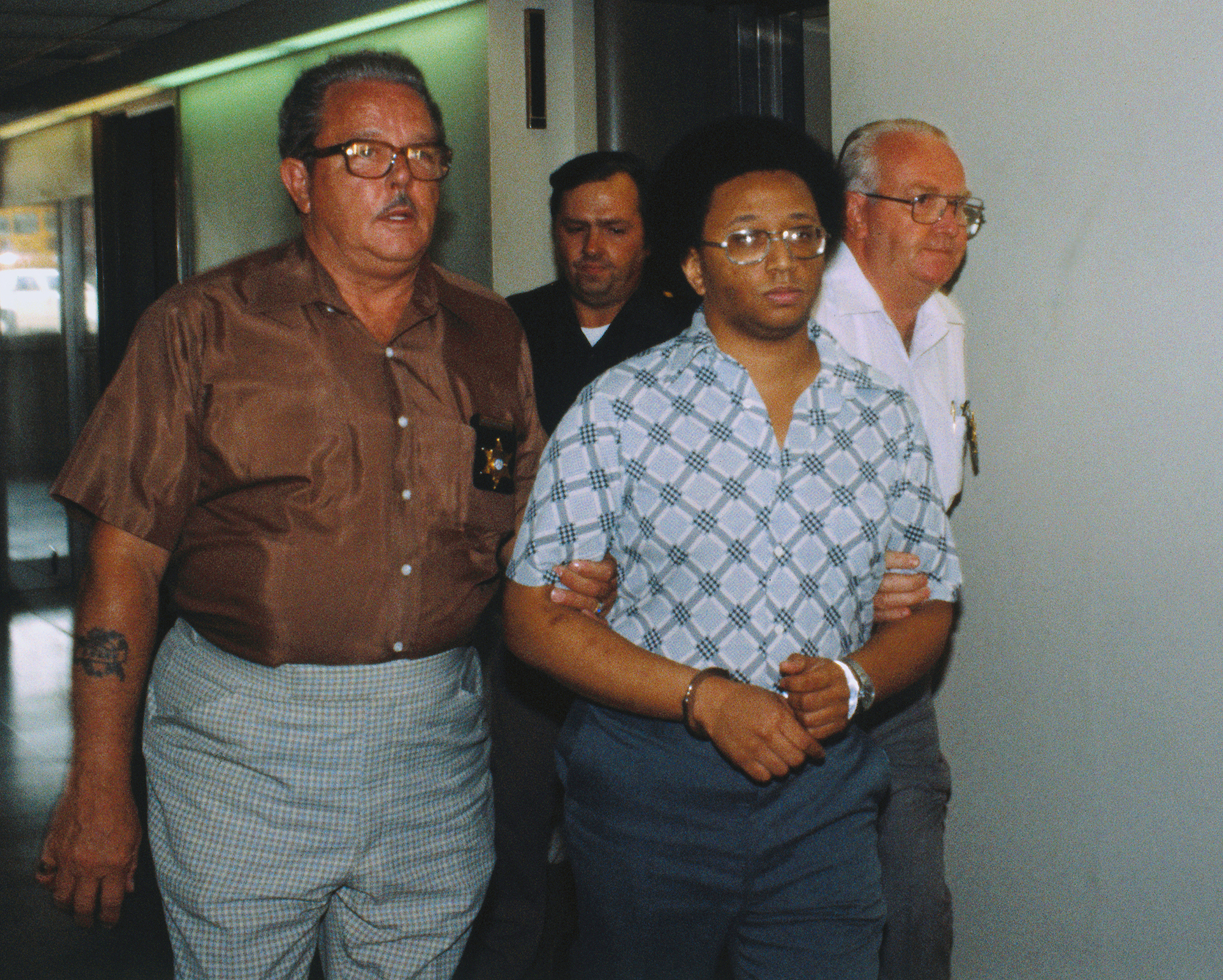 Men Leading Wayne Williams in Handcuffs